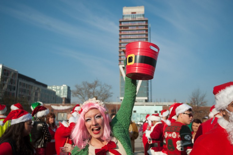 A woman dressed as a Santa's elf collects donations before the start of the annual SantaCon pub crawl December 12, 2015 in the Brooklyn borough of New York City. Hundreds of revelers take part in the holiday pub crawl, though some local bars and businesses have banned participants in an effort to avoid the typically rowdy SantaCon crowds. (Stephanie Keith/Getty Images)