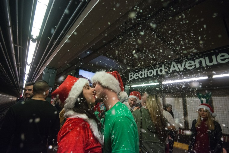 Two people dressed as a Santa share a kiss on the subway platform during the annual SantaCon pub crawl December 12, 2015 in the Brooklyn borough of New York City. Hundreds of revelers take part in the holiday pub crawl, though some local bars and businesses have banned participants in an effort to avoid the typically rowdy SantaCon crowds. (Stephanie Keith/Getty Images)