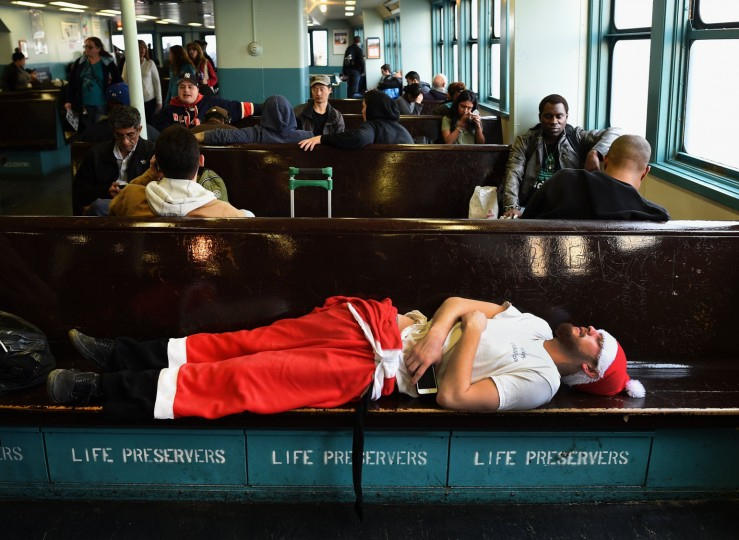 A man dressed in a Santa outfit sleeps on the Staten Island during the SantaCon in New York City on December 12, 2015. SantaCon is an event where groups of men and woman dress as Santa. (Timothy A. Clary/AFP/Getty Images)
