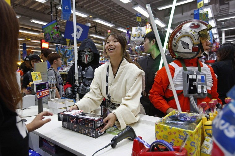 "In this Sept. 4, 2015 file photo, fans dressed as Star Wars characters shop at a toy store at midnight in Hong Kong as part of the global event called ""Force Friday"" to release new toys and other merchandise from the new movie ""Star Wars: The Force Awakens."" (AP Photo/Kin Cheung, File)"