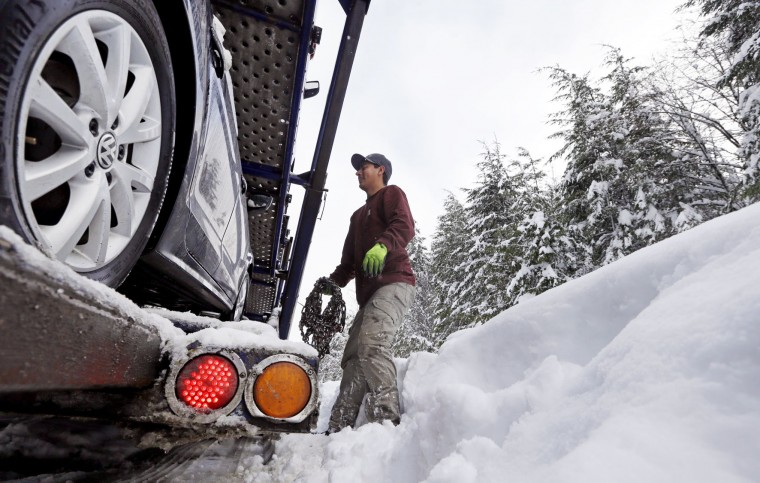 Truck driver Jesse Arevalo, of Yakima, Wash., stows his chains after making the drive across Snoqualmie Pass, Wash., Tuesday, Dec. 22, 2015. A weather pattern that could be associated with El Nino has turned winter upside-down across the U.S. during a week of heavy holiday travel, bringing spring-like warmth to the Northeast, a risk of tornadoes in the South and so much snow in parts of the West that there are concerns about avalanches. (AP Photo/Elaine Thompson)