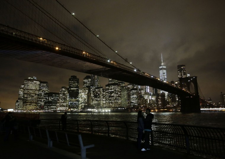 A couple pauses near the Brooklyn Bridge on a warm evening in the Brooklyn borough of New York on Tuesday, Dec. 22, 2015. A weather pattern partly linked with El Nino has turned winter upside-down across the U.S. during a week of heavy holiday travel, bringing spring-like warmth to the Northeast, a risk of tornadoes in the South and so much snow across the West that even skiing slopes have been overwhelmed. (AP Photo/Peter Morgan)