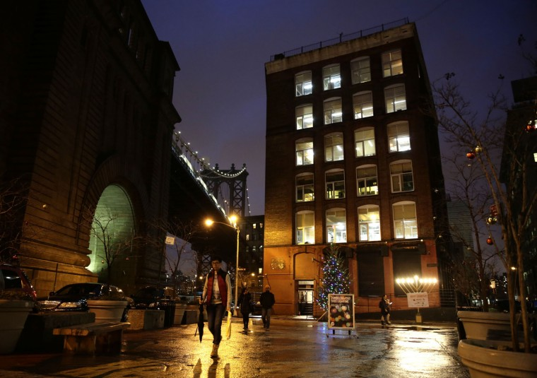 A man walks through a plaza on a warm evening in the Brooklyn borough of New York on Tuesday, Dec. 22, 2015. In a reversal of a typical Christmas, forecasters expect New York to be in the mid-60s on the Christmas holiday — several degrees higher than Los Angeles. (AP Photo/Peter Morgan)