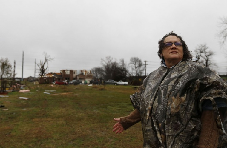 Evelyn Lindstrom looks for her cat that ran away as her home, seen behind her, was damaged by Saturday night's tornado in Copeville, Texas, Sunday, Dec. 27, 2015. Tornadoes that swept through the Dallas area caused substantial damage and at least 11 people died either from the storm or related traffic accidents and dozens of people were injured. (Rachel Woolf/The Dallas Morning News via AP)