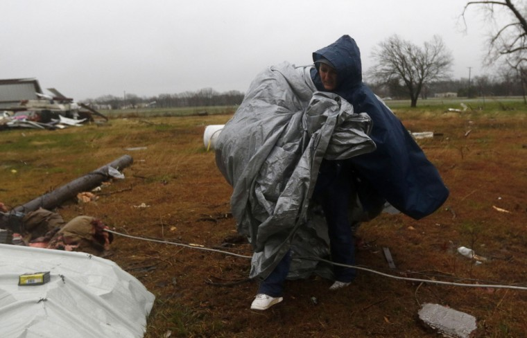 Alicia Aldridge carries tarp over broken telephone wires while working on fixing Rocky Haddick's, not pictured, roof, off of TX-78 in Copeville, Texas, on Sunday, Dec. 27, 2015, after heavy rain, high winds and tornadoes swept through North Texas the previous night. (Rachel Woolf/Dallas Morning News/TNS)
