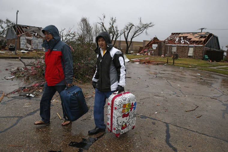 Thomas Khien, left, and Sokhay Vissal carry luggage from their aunt's home on Sunday, Dec. 27, 2015, after a tornado hit Saturday night on Willard Street in Rowlett, Texas. (Nathan Hunsinger/Dallas Morning News/TNS)