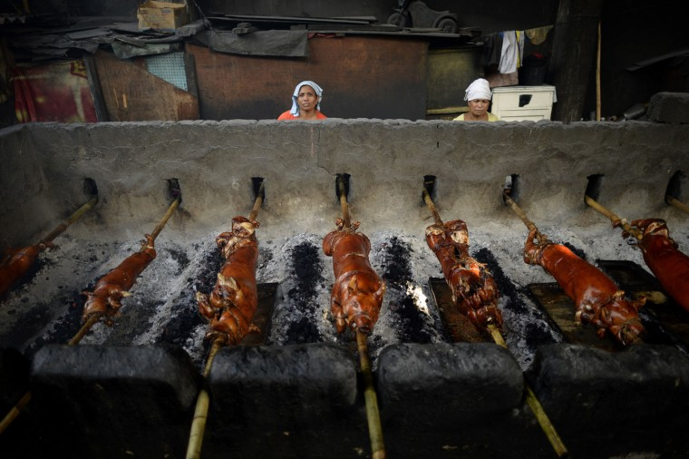 "Workers rotate bamboo skewered pigs as they are roasted over hot coals in Manila on December 23, 2015. ""Lechon"", or roasted pig, has always been regular fare at Philippine festivities, especially during Christmas and New Year celebrations. The Philippine Christmas season runs from December until the second week of January. (Noel Celis/AFP/Getty Images)"