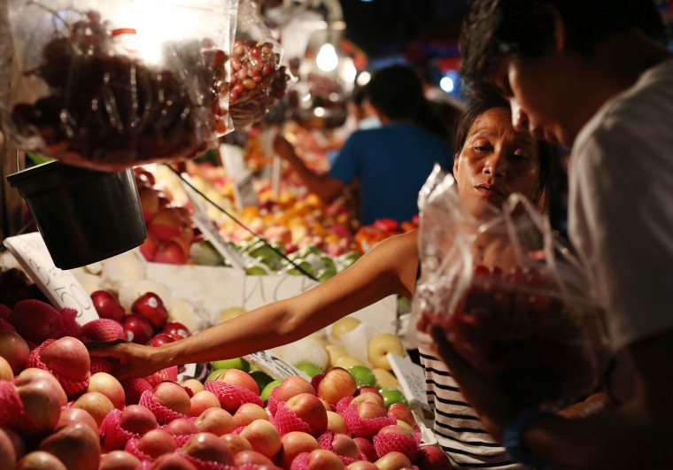 A Filipino woman vendor sells round fruits along makeshift stalls in downtown Manila, Philippines on Monday, Dec. 28, 2015. Many Filipinos believe that having 12 round fruits of different kinds on the family table will bring good luck during the New Year. (AP Photo/Aaron Favila)