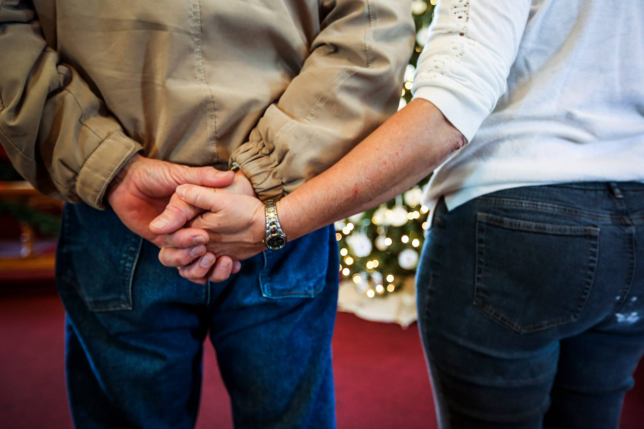 A couple holds hands during a service on Tangier Island. (Kaitlin Newman/For The Baltimore Sun)
