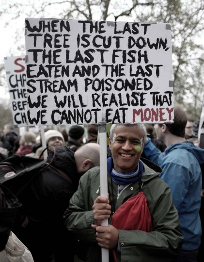 "A protester holds a placard quoting a Native American saying - ""When the last tree has been cut down, the last fish caught, the last river poisoned, only then will we realize that one cannot eat money.""  According to  Alisdare Hickson, who shot the image, he was participating in the climate change march in London on 29 November which was held as part of a series of rallies worldwide prior to the COP21 Paris climate change talks. Activists want decisive action to limit the rise in average global temperature to 2 degrees celcius above pre-industrial levels.  Protesters in Paris were largely silenced by a demonstration ban, though some found creative measures around the edict.   Note: This is a flickr image released under a Creative Commons license. Caption information has not been vetted by The Sun. Full credit and license information: http://bit.ly/1RtAHl9"