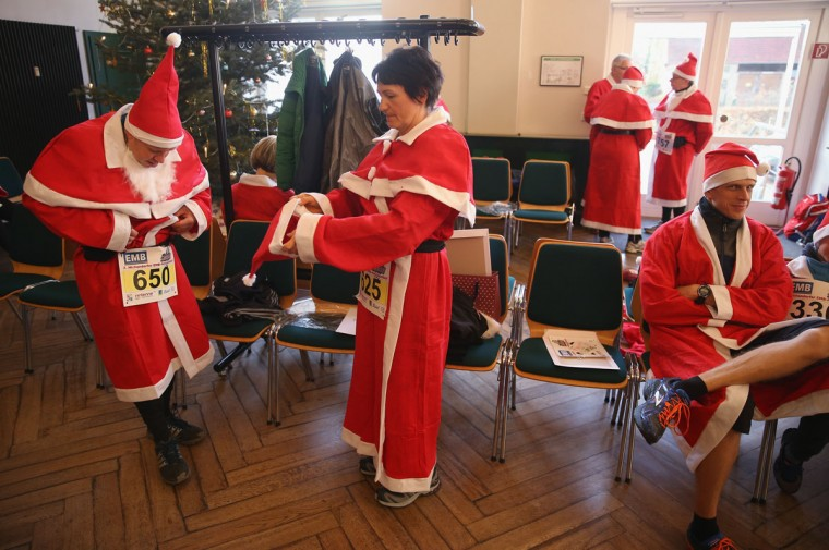 Participants dressed as Santa Claus dress into their costumes before taking part in the 7th annual Michendorf Santa Run on December 6, 2015 in Michendorf, Germany. A record 900 runners took part in this year's event, which included 2,5km, 5km and 10km races. (Photo by Sean Gallup/Getty Images)