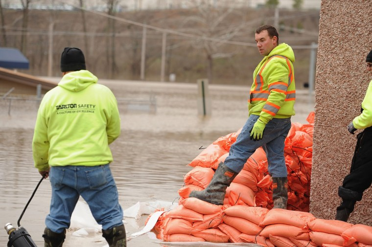 Workers work to install sandbags outside a business on December 30, 2015 in Fenton, Missouri. The St. Louis area and surrounding region experiencing record flood crests of the Mississippi, Missouri and Meremac Rivers after days of record rainfall. (Photo by Michael B. Thomas/Getty Images)