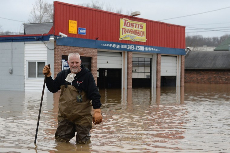 John Tosti, owner of Tosti's Transmission wades in the water after inspecting his business as it takes on floodwater on December 30, 2015 in Fenton, Missouri. The St. Louis area and surrounding region experiencing record flood crests of the Mississippi, Missouri and Meremac Rivers after days of record rainfall. (Photo by Michael B. Thomas/Getty Images)