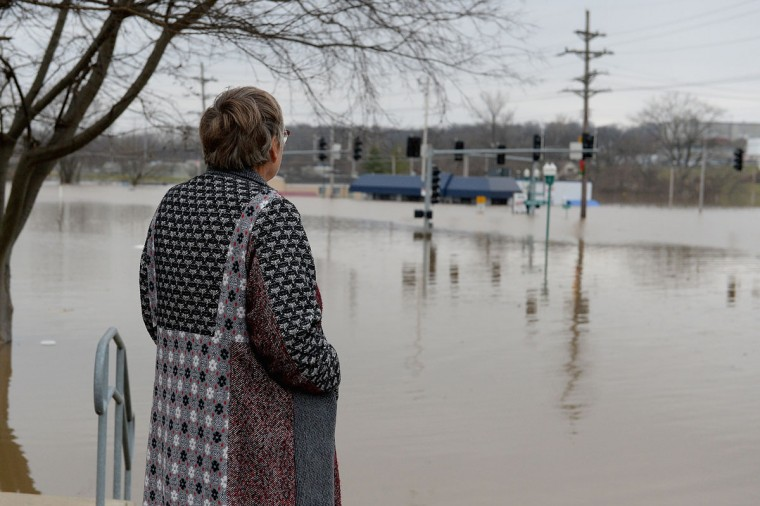 A woman looks on as floodwaters rise on Gravois Road on December 30, 2015 in Fenton, Missouri. The St. Louis area and surrounding region experiencing record flood crests of the Mississippi, Missouri and Meremac Rivers after days of record rainfall. (Photo by Michael B. Thomas/Getty Images)