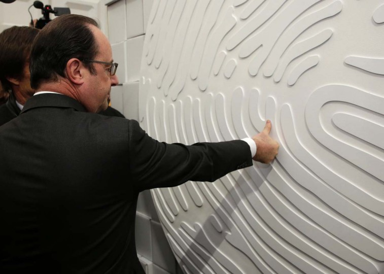 French President Francois Hollande puts his thumbprint on a wall at the Nicolas Hulot Foundation stand in the Climate Generations area, as part of the World Climate Change Conference 2015 (COP21), at Le Bourget on the outskirts of the French capital Paris.  AFP/Getty Images