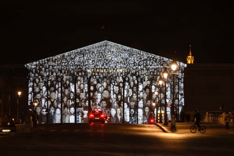 A picture taken on November 30, 2015 shows images of more than 500 people being projected onto the facade of the French National Assembly building during the 2015 UN Climate Change Conference (COP21) in Paris.  The Standing March is the collaborative work by the French artist known as JR and US filmmaker Darren Aronofsky. Many protesters in Paris were largely silenced by a demonstration ban this week, though some found creative measures around the edict. ERIC FEFERBERG - AFP/Getty Images
