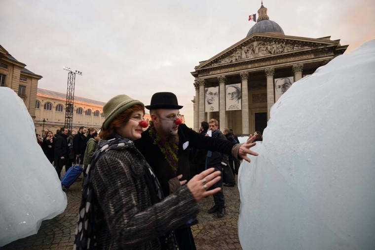 "Two people wearing red clown noses look at an art installation by a Danish-Icelandic artist entitled ""Ice Watch"", made with parts of Greenland's ice cap, on display in front of the Pantheon in Paris on December 3, 2015.   The installation by Olafur Eliasson is part of a project presented during the World Climate Change Conference 2015 (COP21), the United Nations conference on climate change taking place at le Bourget, on the outskirts of Paris, from November 30 to December 11. ERIC FEFERBERG - AFP/Getty Images"