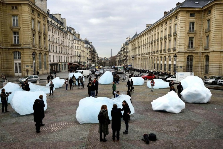 "People look at an art installation by a Danish-Icelandic artist entitled ""Ice Watch"", made with parts of Greenland's ice cap, on display in front of the Pantheon in Paris on December 3, 2015.   The installation by Olafur Eliasson is part of a project presented during the World Climate Change Conference 2015 (COP21), the United Nations conference on climate change taking place at le Bourget, on the outskirts of Paris, from November 30 to December 11. ERIC FEFERBERG - AFP/Getty Images"