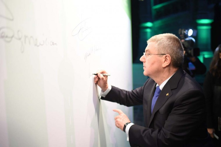 USOC Chairman Thomas Bach signs a white wall during a summit on climate with local elected leaders on December 4, 2015 at the Paris town hall, as part of the World Climate Change Conference 2015 (COP21), at Le Bourget on the outskirts of the French capital Paris.   STEPHANE DE SAKUTIN - AFP/Getty Images