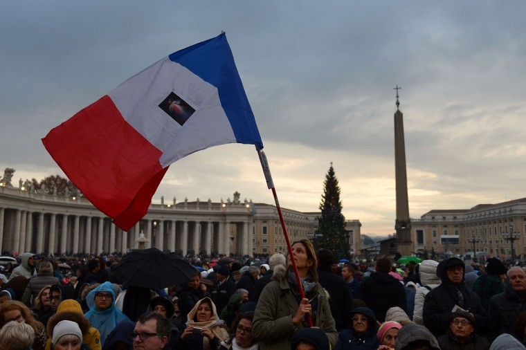 """A pilgrim waves a French national flag on St Peter's square before the start of the Jubilee Year of Mercy, on December 8, 2015 in Vatican. Pope Francis marks the start of an extraordinary Jubilee year for the world's 1.2 billion Catholics by opening a """"Holy Door"""" in the walls of St Peter's basilica. At 9.30 am (0830 GMT), the Argentinian pontiff will pronounce the words """"Aperite mihi Porta Iustitiae"""" -- Latin for """"open to me the gates of justice"""" -- and the door, which is normally bricked up, will be opened. (AFP Photo/Vincenzo Pinto)"""