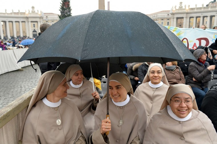 """Nuns wait at St Peter's square before the start of the Jubilee Year of Mercy, on December 8, 2015 in Vatican. Pope Francis marks the start of an extraordinary Jubilee year for the world's 1.2 billion Catholics by opening a """"Holy Door"""" in the walls of St Peter's basilica. At 9.30 am (0830 GMT), the Argentinian pontiff will pronounce the words """"Aperite mihi Porta Iustitiae"""" -- Latin for """"open to me the gates of justice"""" -- and the door, which is normally bricked up, will be opened. (AFP Photo/Alberto Pizzoli)"""