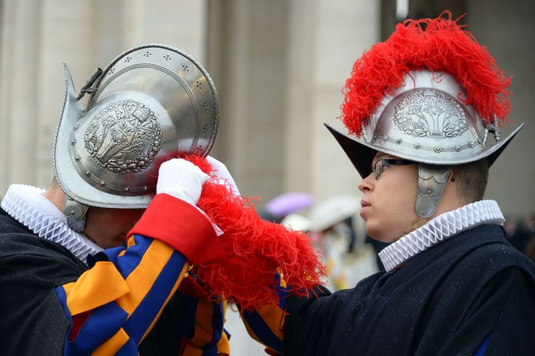 """A Swiss guard helps a colleague to adjust his helmet at St Peter's square before the start of the Jubilee Year of Mercy, on December 8, 2015 in Vatican. Pope Francis marks the start of an extraordinary Jubilee year for the world's 1.2 billion Catholics by opening a """"Holy Door"""" in the walls of St Peter's basilica. At 9.30 am (0830 GMT), the Argentinian pontiff will pronounce the words """"Aperite mihi Porta Iustitiae"""" -- Latin for """"open to me the gates of justice"""" -- and the door, which is normally bricked up, will be opened. (AFP Photo/Vincenzo Pinto)"""