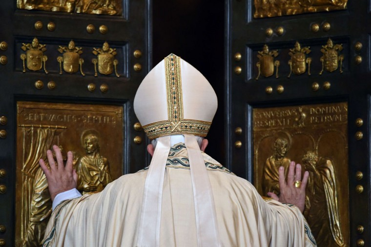 """Pope Francis opens a """"Holy Door"""" at St Peter's basilica to mark the start of the Jubilee Year of Mercy, on December 8, 2015 in Vatican. In Catholic tradition, the opening of """"Holy Doors"""" in Rome symbolises an invitation from the Church to believers to enter into a renewed relationship with God. (AFP Photo/Vincenzo Pinto)"""