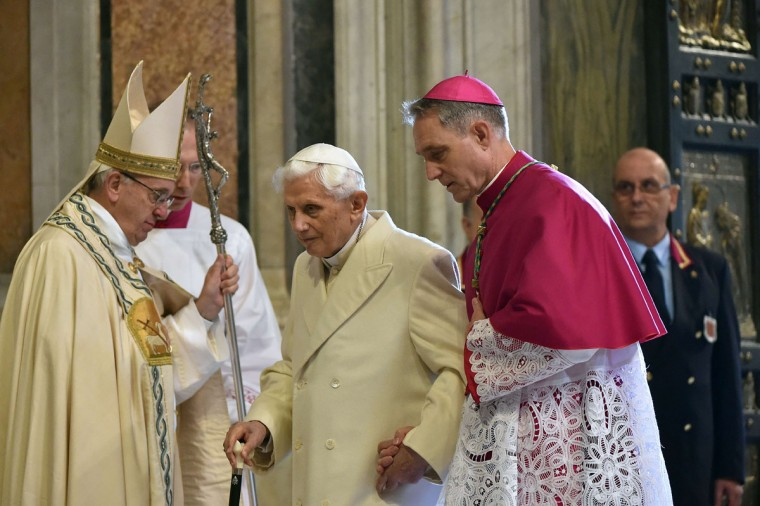 """Pope Emeritus Benedict XVI (C) is helped by the prefect of the papal household Georg Gaenswein (R) as he walks past Pope Francis in St Peter's basilica after the opening of the """"Holy Door"""" to mark the start of the Jubilee Year of Mercy, on December 8, 2015 in Vatican. Pope Francis marks the start of an extraordinary Jubilee year for the world's 1.2 billion Catholics by opening a """"Holy Door"""" in the walls of St Peter's basilica. At 9.30 am (0830 GMT), the Argentinian pontiff will pronounce the words """"Aperite mihi Porta Iustitiae"""" -- Latin for """"open to me the gates of justice"""" -- and the door, which is normally bricked up, will be opened. (AFP Photo/Alberto Pizzoli)"""