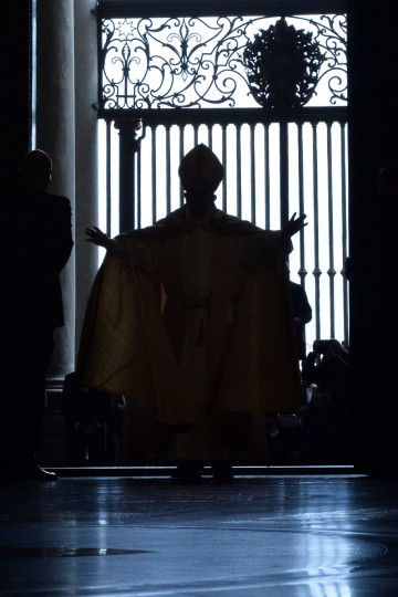 """Pope Francis opens a """"Holy Door"""" at St Peter's basilica to mark the start of the Jubilee Year of Mercy, on December 8, 2015 in Vatican. In Catholic tradition, the opening of """"Holy Doors"""" in Rome symbolises an invitation from the Church to believers to enter into a renewed relationship with God. (AFP Photo/Alberto Pizzoli)"""