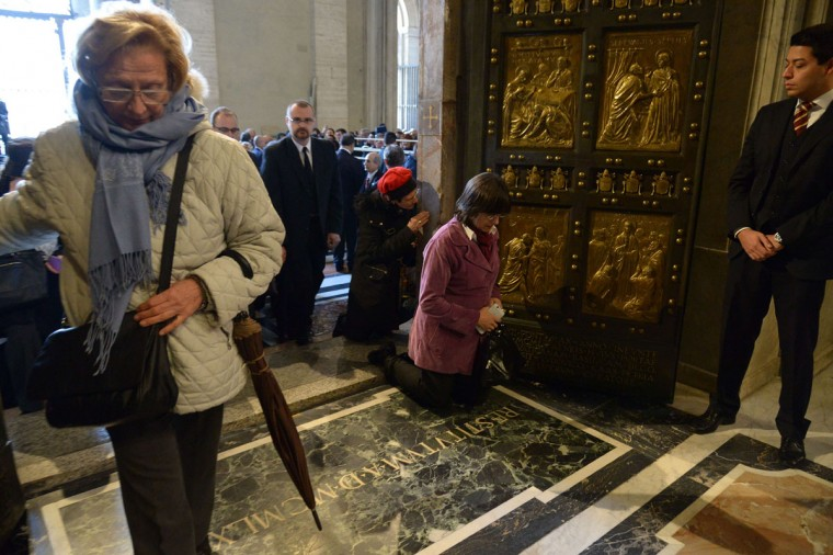"""Worshipers pass by the """"Holy Door"""" opened by Pope Francis at St Peter's basilica to mark the start of the Jubilee Year of Mercy, on December 8, 2015 in Vatican. In Catholic tradition, the opening of """"Holy Doors"""" in Rome symbolises an invitation from the Church to believers to enter into a renewed relationship with God. (AFP Photo/Vincenzo Pinto)"""