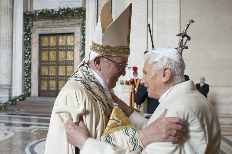 """This handout picture released by the Vatican press office shows Pope Francis (L) welcoming Pope emeritus Benedict XVI before the opening of the """"Holy Door"""" to mark the start of the Jubilee Year of Mercy, on December 8, 2015 in Vatican. Pope Francis marks the start of an extraordinary Jubilee year for the world's 1.2 billion Catholics by opening a """"Holy Door"""" in the walls of St Peter's basilica. At 9.30 am (0830 GMT), the Argentinian pontiff will pronounce the words """"Aperite mihi Porta Iustitiae"""" -- Latin for """"open to me the gates of justice"""" -- and the door, which is normally bricked up, will be opened. (AFP Photo/Osservatore Romano)"""