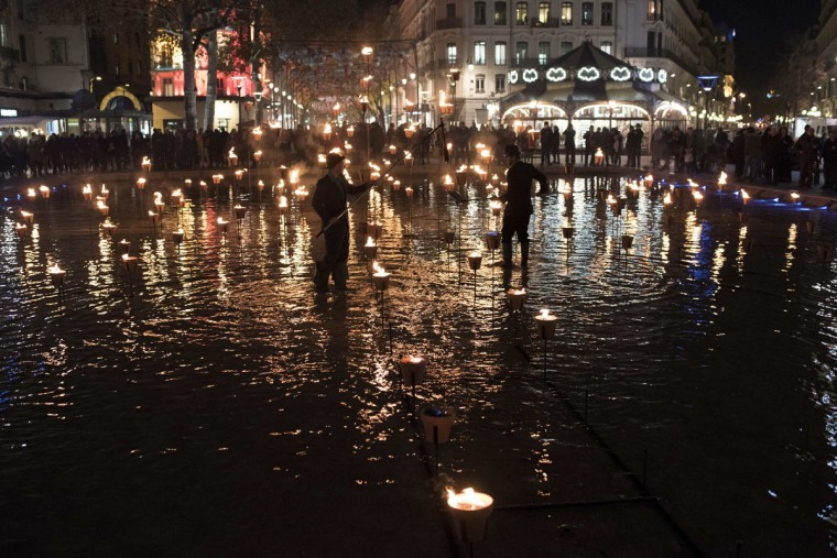 Members of the public gather as two men light a candle display on December 8, 2015 in Lyon, in tribute to victims of the November 13 Paris terrorist attacks, and as a replacement for the cancelled annual Festival of Lights, a secular version of a religious tradition devoted to the Virgin Mary and dating back to 153 years ago. (AFP Photo/Jean-Philippe Ksiazek)