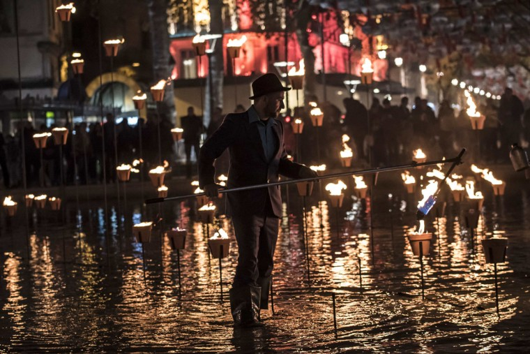 A man lights a candle display on December 8, 2015 in Lyon, in tribute to victims of the November 13 Paris terrorist attacks, and as a replacement for the cancelled annual Festival of Lights, a secular version of a religious tradition devoted to the Virgin Mary and dating back to 153 years ago. (AFP Photo/Jean-Philippe Ksiazek)