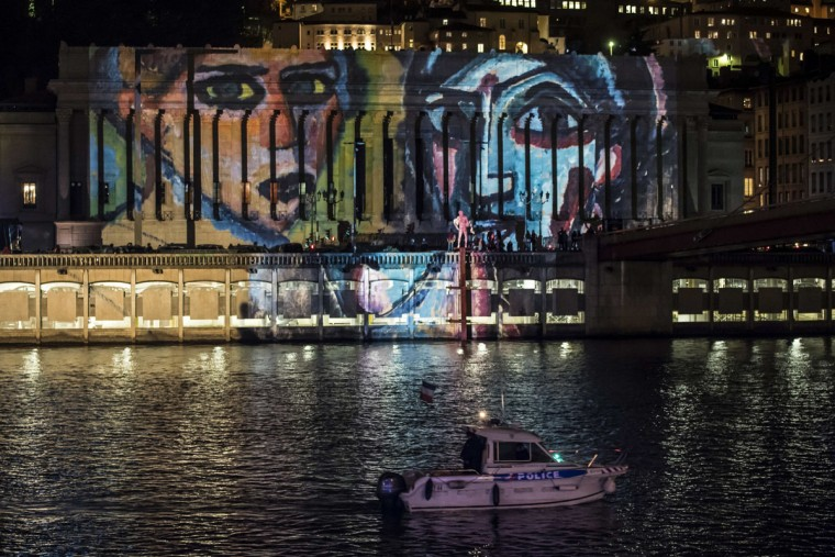 """This photo taken on December 8, 2015 in Lyon shows the light installation """"Regards"""" by Daniel Knipper, in tribute to victims of the November 13 Paris terrorist attacks, and as a replacement for the cancelled annual Festival of Lights, a secular version of a religious tradition devoted to the Virgin Mary and dating back to 153 years ago. (AFP Photo/Jean-Philippe Ksiazek)"""