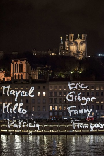 "This photo taken on December 8, 2015 in Lyon shows the light installation ""Regards"" by Daniel Knipper, in tribute to victims of the November 13 Paris terrorist attacks, and as a replacement for the cancelled annual Festival of Lights, a secular version of a religious tradition devoted to the Virgin Mary and dating back to 153 years ago. (AFP Photo/Jean-Philippe Ksiazek)"