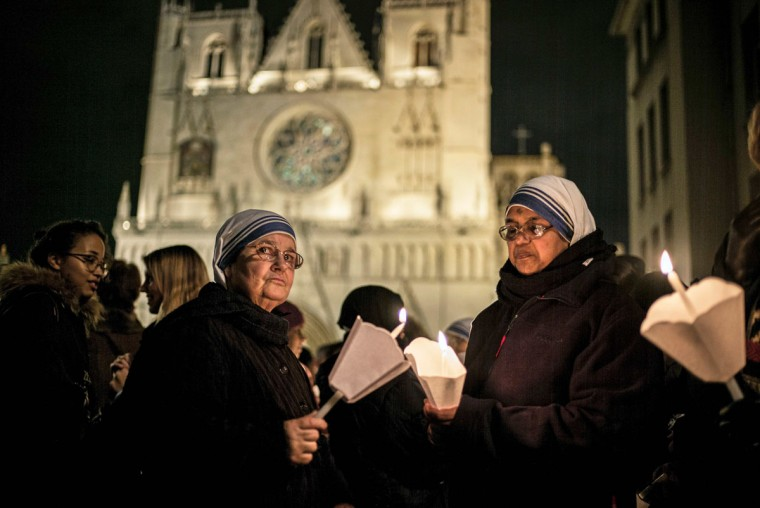 Two nuns look on while holding candles on December 8, 2015 in Lyon, as part of a tribute to victims of the November 13 Paris terrorist attacks, and as a replacement for the cancelled annual Festival of Lights, a secular version of a religious tradition devoted to the Virgin Mary and dating back to 153 years ago. (AFP Photo/Jeff Pachoud)