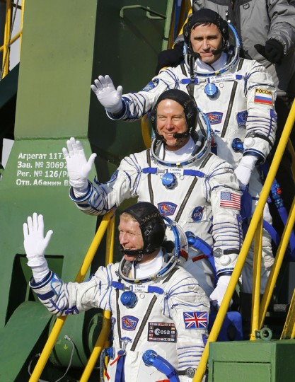 British astronaut Tim Peake (bottom), Russian cosmonaut Yuri Malenchenko (top) and U.S. astronaut Tim Kopra wave as they board the Soyuz TMA-19M spacecraft at the Russian-leased Baikonur cosmodrome, prior to blasting off to the International Space Station on Tuesday. (SHAMIL ZHUMATOV/AFP/Getty Images)