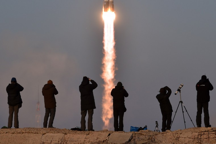 Photographers take pictures as Russia's Soyuz TMA-19M spacecraft carrying the International Space Station Expedition 46/47 crew blasts off. (KIRILL KUDRYAVTSEV/AFP/Getty Images)
