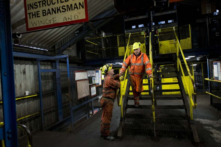 Banksman Joe Murray (R) speaks to a coal miner after opening the lift carrying the final shift of miners at the Kellingley Colliery in Yorkshire, northern England, on December 18, 2015. The shutdown of the mine in Yorkshire in northern England closes a 200-year chapter of Britain's industrial history.  || CREDIT: OLI SCARFF - AFP/GETTY IMAGES