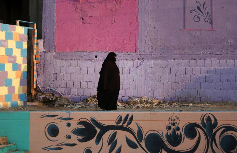 A Palestinian woman walks past a house painted by Palestinian artists in the al-Shati refugee camp in Gaza City, on December 19, 2015. (AFP Photo/Mahmud Hams)