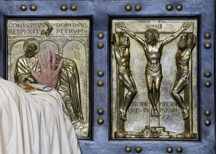 Pope Francis pushes open the Holy Door of St. Peter's Basilica, formally launching the Holy Year of Mercy, at the Vatican, Tuesday, Dec. 8, 2015. Pope Francis pushed open the great bronze doors of St. Peter's Basilica to launch his Holy Year of Mercy, declaring that mercy trumps moralizing in his Catholic Church. (AP Photo/Gregorio Borgia)
