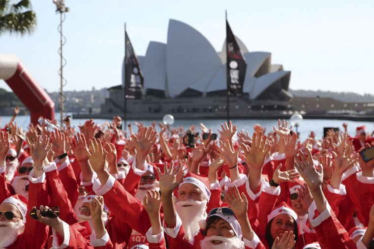 Thousands of people dressed as Santa Claus pose for a photo before taking to the streets for the annual Santa Fun Run in Sydney Sunday, Dec. 6, 2015. The Santa Fun Run was organized by Variety, an Australian charity that helps children who are sick, disadvantaged or have special needs. (AP Photo/Rob Griffith)