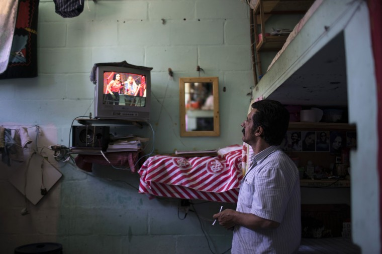 In this Nov. 30, 2015 photo, an inmate watches television in a cell block for prisoners who are part of a work program at the Central Prison in Porto Alegre, Brazil. Inmates on work programs, voluntarily detoxing from drugs or from the LGBT community who are at high risk of being attacked, live in separate areas of the prison, but their special protection is unquestionably an exception. (AP Photo/Felipe Dana)