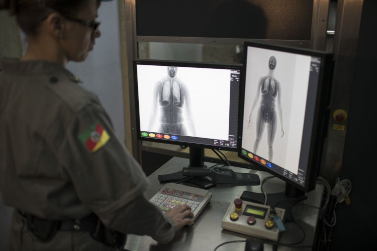 In this Dec. 1, 2015 photo, a police officer inspects an image of a visitor standing inside a body scanner at the Central Prison in Porto Alegre, Brazil. The recently installed scanner has reduced the number of cell phones, drugs and razor blades that are smuggled into the prison by visiting relatives. But many of these items are often thrown over the prison walls and retrieved by waiting inmates. (AP Photo/Felipe Dana)