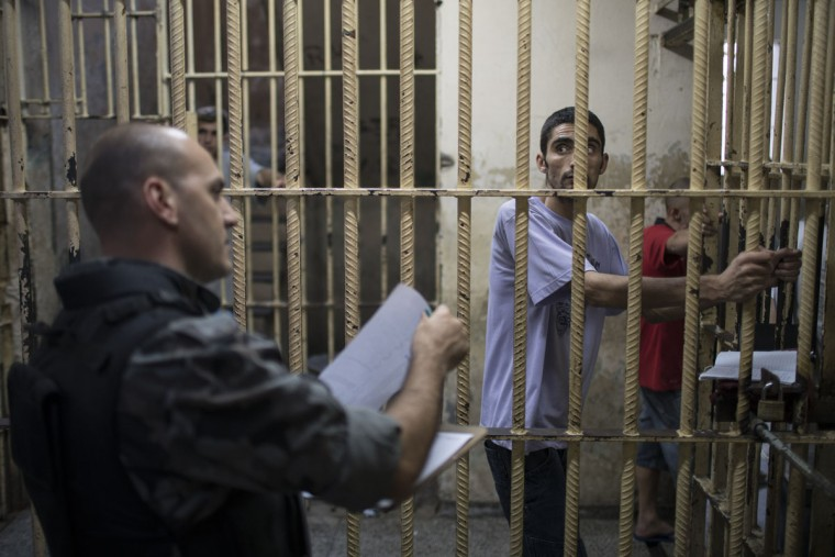 In this Dec. 1, 2015 photo, an inmate watches a police officer take a prisoner count inside the Central Prison in Porto Alegre, Brazil. Prisoners are housed in different cells according to which gangs they belong to in an effort to tamp down violence. (AP Photo/Felipe Dana)
