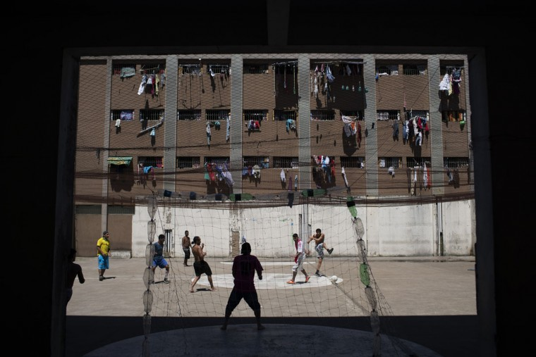 In this Nov. 30, 2015 photo, inmates play soccer at the Central Prison in Porto Alegre, Brazil, where inmates' clothing hang from their cell windows. The facility holds over twice its capacity of almost 2000 inmates. (AP Photo/Felipe Dana)