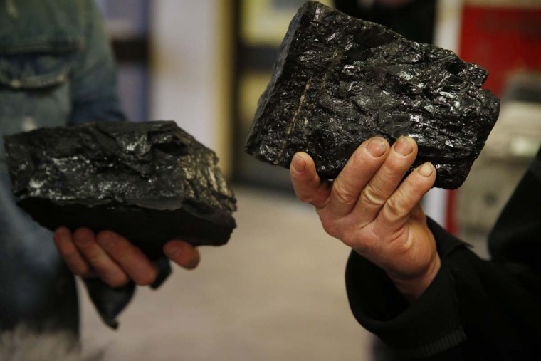 Miners at Kellingley Colliery hold lumps of coal they are keeping as mementoes of their last day working at the colliery in Knottingley, northern England, as the final shift works underground, Friday Dec. 18, 2015.Once, coal fueled the British Empire, employed armies of men and shook the power of governments. On Friday, workers at Britain's last operating deep coal mine finish their final shift. The last haul of coal from the pit is destined for a museum, as a once-mighty industry fades into history. (John Giles/PA via AP)