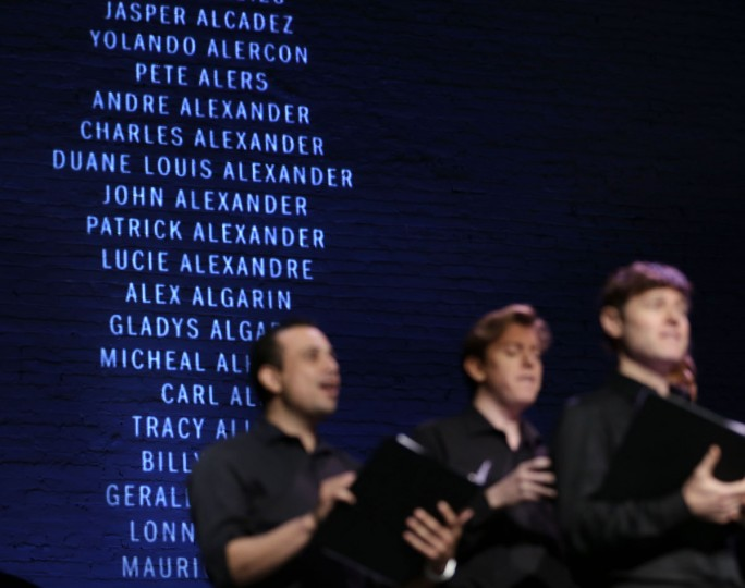 Members of the NYC Gay Men's Choir sing while a list of names of people who died, most from AIDS/HIV complications, is projected on the wall during an event on World AIDS Day at the Apollo Theater in New York, Tuesday, Dec. 1, 2015. New York state will dedicate $200 million more to its $2.5 billion effort to end the AIDS epidemic by 2020. It is already reporting significant milestones: no new cases of mother-to-child transmission were reported in the past year, the first time that's happened since the epidemic began. (AP Photo/Seth Wenig)