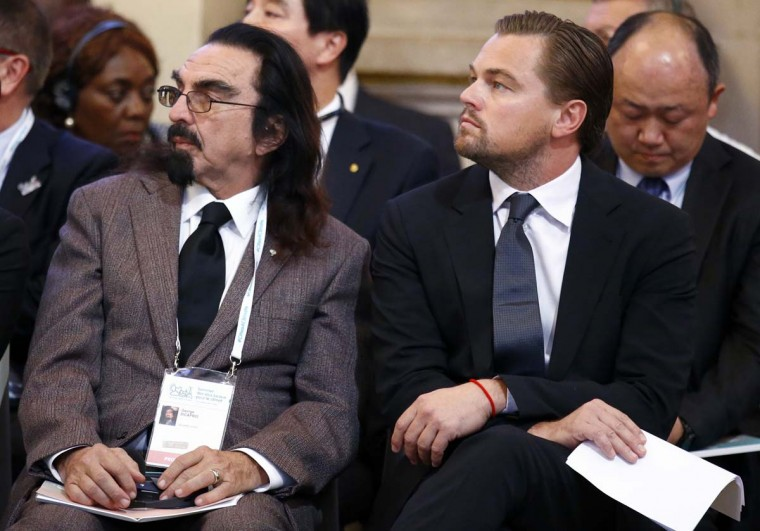 Leonardo DiCaprio, right, and his brother George Di Caprio, left listen to speeches during a meeting with Mayors to push for local actions to fight climate change at Paris city Hall on the margins of the COP21, as part of the COP21, United Nations Climate Change Conference, in Paris, Friday, Dec. 4, 2015. Many protesters in Paris were  silenced by a demonstration ban this week, though some found creative measures around the edict.  || CREDIT: FRANCOIS MORI - AP PHOTO