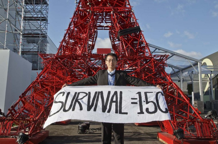 A representative of an NGO displays a banner in front of a reproduction of the Eiffel tower at the COP21, United Nations Climate Change Conference, in Le Bourget north of Paris, Friday, Dec. 4, 2015. Many activists and negotiators from small island nations want a final climate accord to aim at a keeping global warming to 1.5 degrees worldwide by 2100, instead of 2 degrees. Some protesters in Paris were  silenced by a demonstration ban this week, though others found creative measures around the edict.  (AP PhotoMichel Euler)